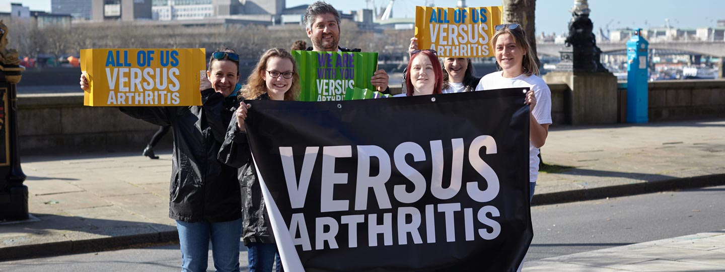 Six supporters of Versus Arthritis holding signs of encouragement up.