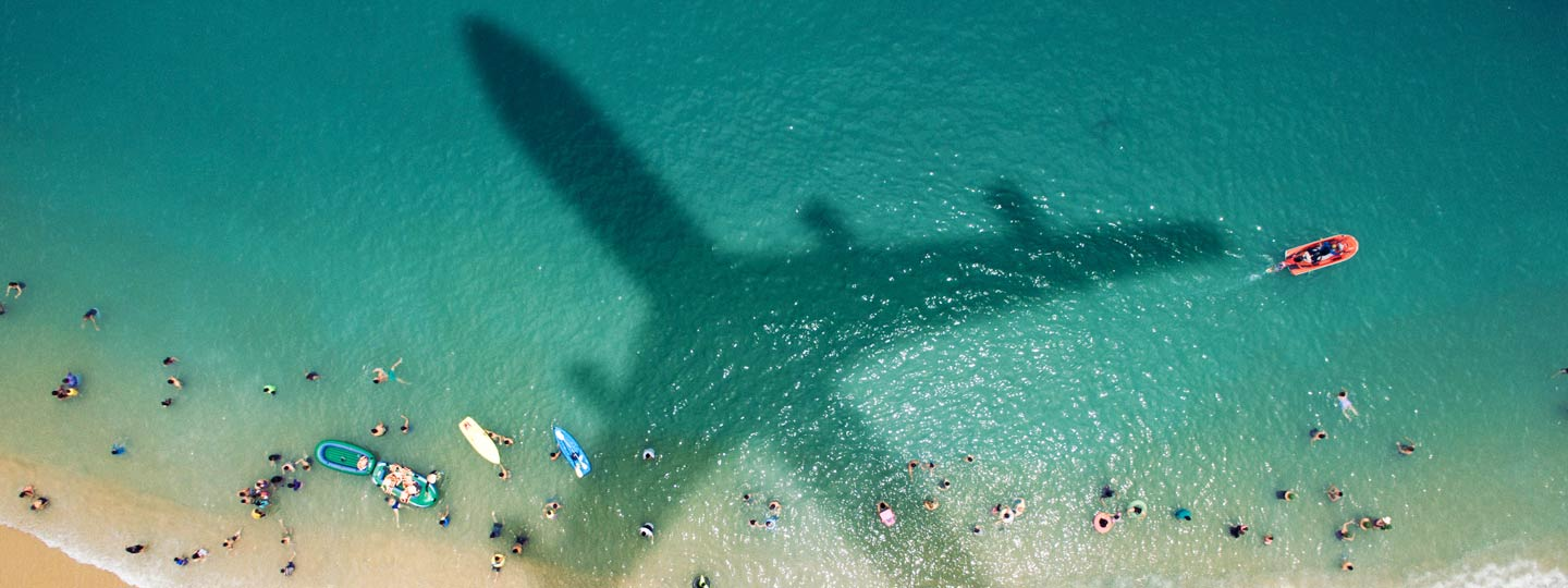 An aeroplane flying over a beach casting it's shadow on the people below.
