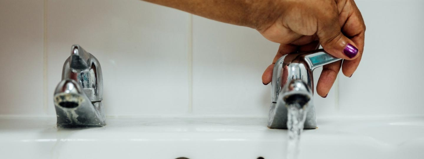 Lady turning on bath tap with help of aids and adaptations.