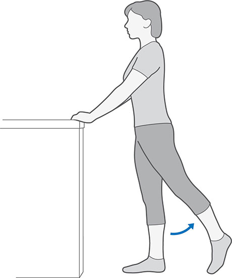 An illustration of someone standing whilst holding onto a table, moving their leg backwards and keeping it straight.
