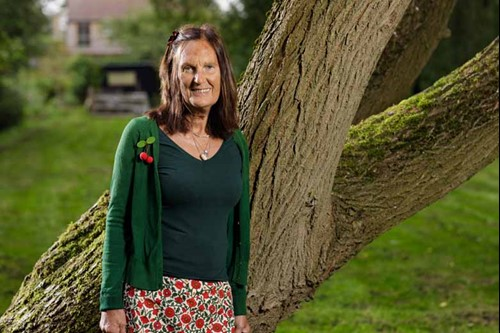 Louise, who has had an hip replacement, stood outside next to a tree.