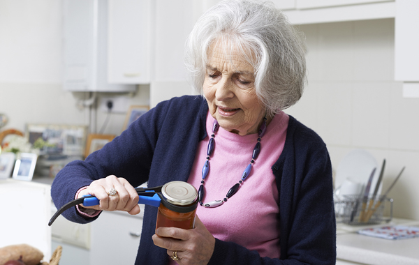 An elderly lady in her kitchen using a gadget to open a jar of food.