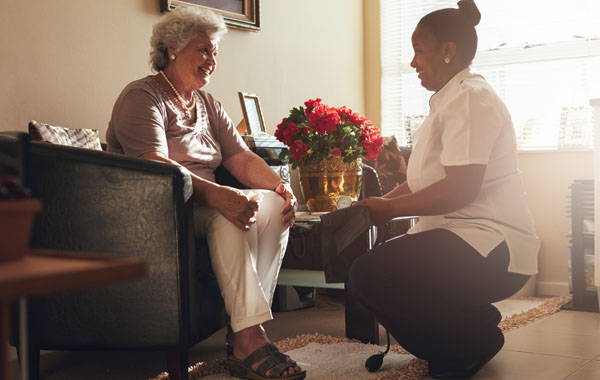 A nurse talking to an elderly patient in her own home.