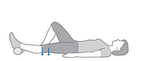 An image of someone laying on their back, with a support under one ankle, pushing their thigh towards the floor.