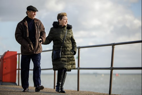 Maureen and her partner Brian walking on the seafront.
