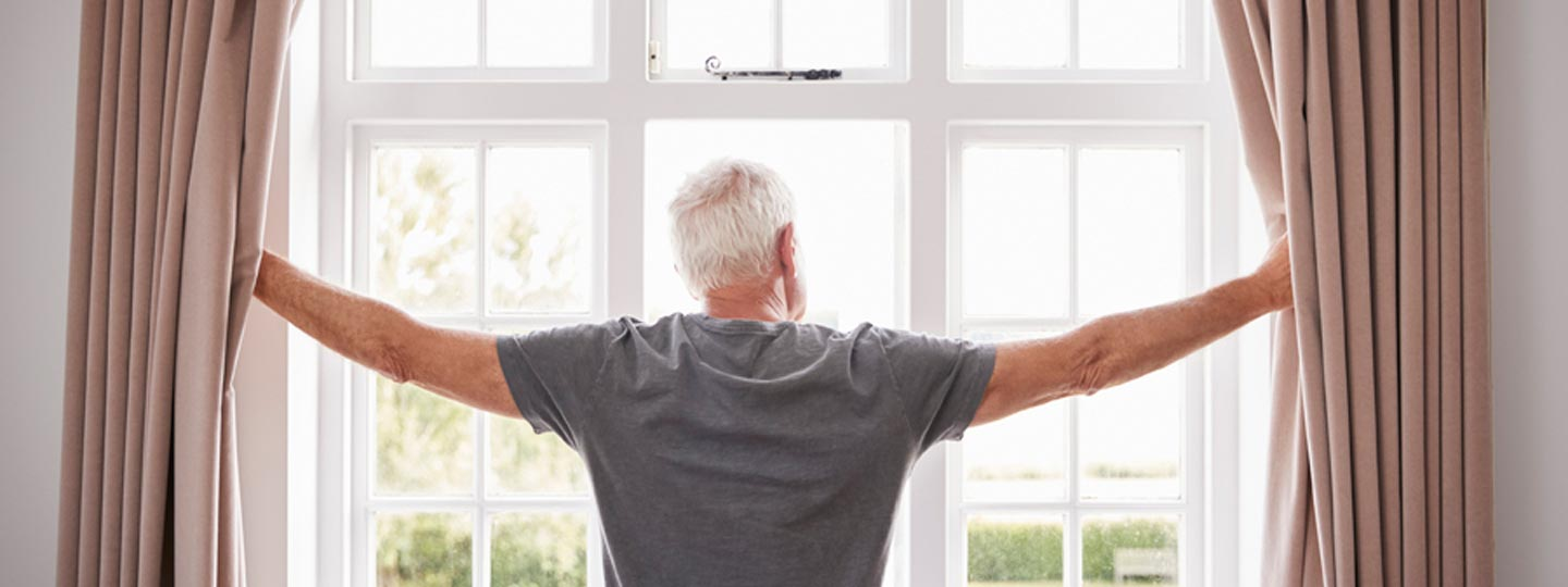 An older man standing at a window drawing back the curtains