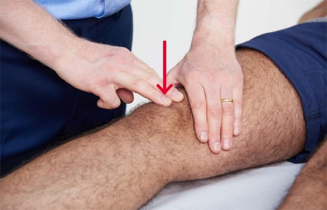 A doctor examining a knee joint.