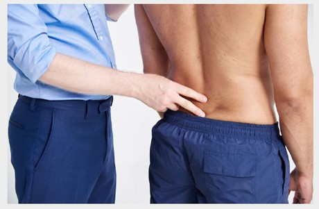 A doctor examining a mans back while he's stood straight.