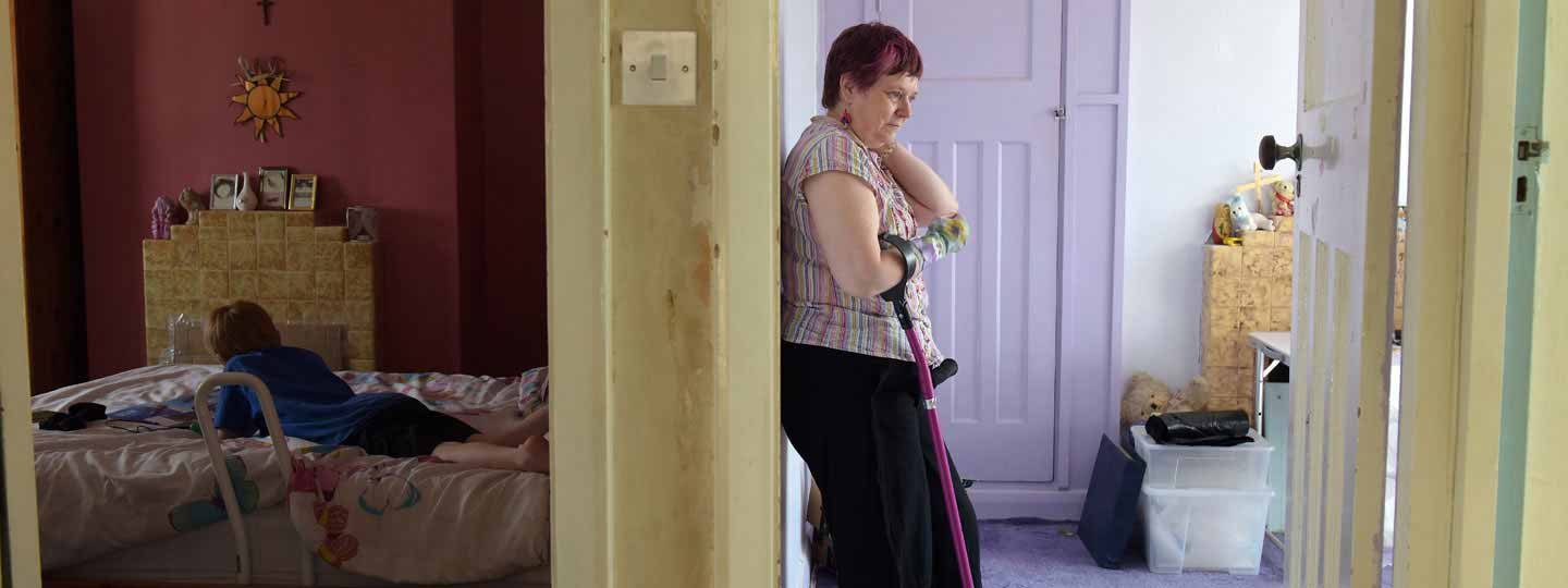 Gillian stood in a bedroom with her crutch for support while her young relative is in the bedroom adjacent.