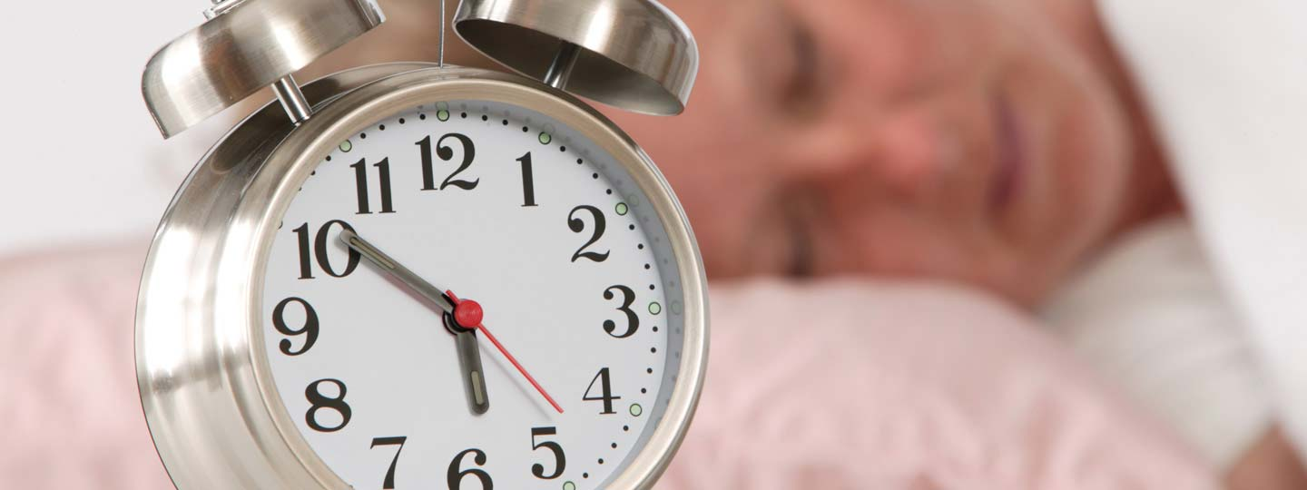 An alarm clock in front of a sleeping woman.