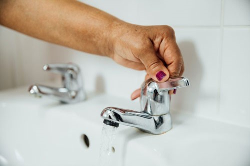 A lady using a easy use tap to fill up a sink.